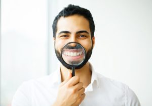 young man using magnifying glass to showcase his dental implants in Coral Springs